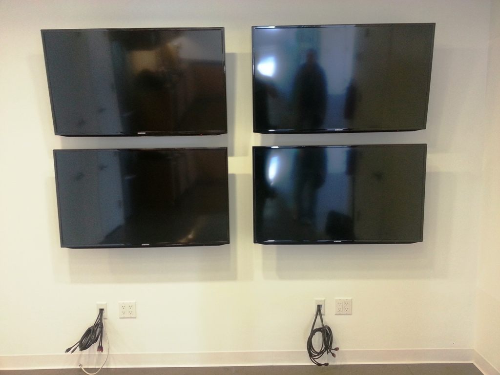 Four out of 17 TVs mounted on the wall in comercial building of Manhattan, NY