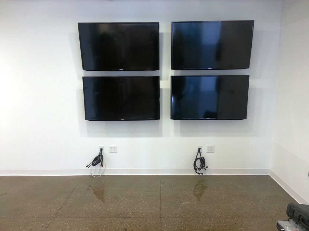 four Samsung TVs mounted on the wall in comercial building of Manhattan, NY