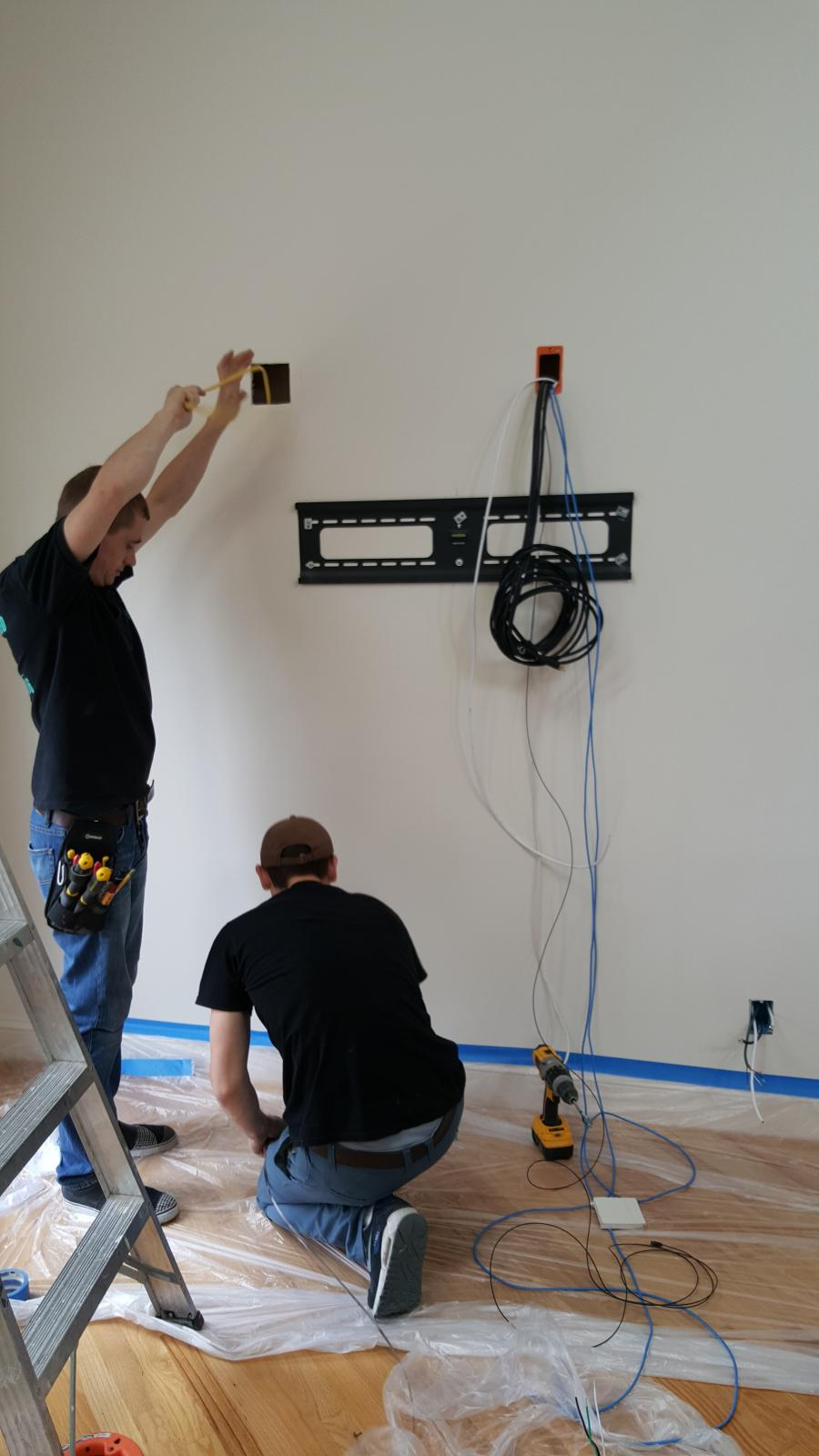 The technicians preparing a wall mount for the 70inch 4K Sony XBR TV - Home Theater Installation With 3.1 Sound Bar, In-wall Sub-Woofer