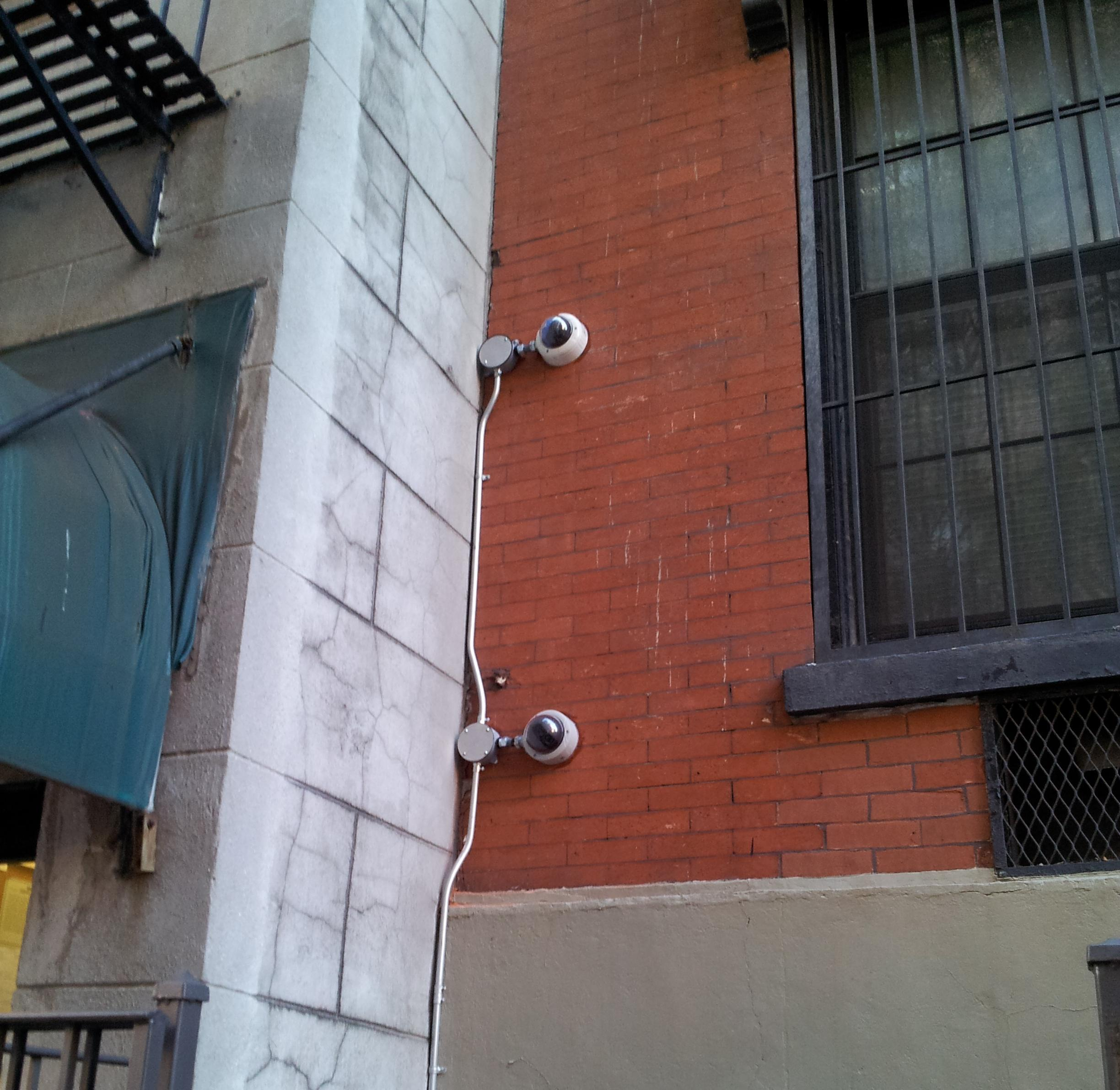 Aluminum pipes to protect two Honeywell CCTV cameras mounted on building wall of residential building of Upper West Side in Manhattan, NY