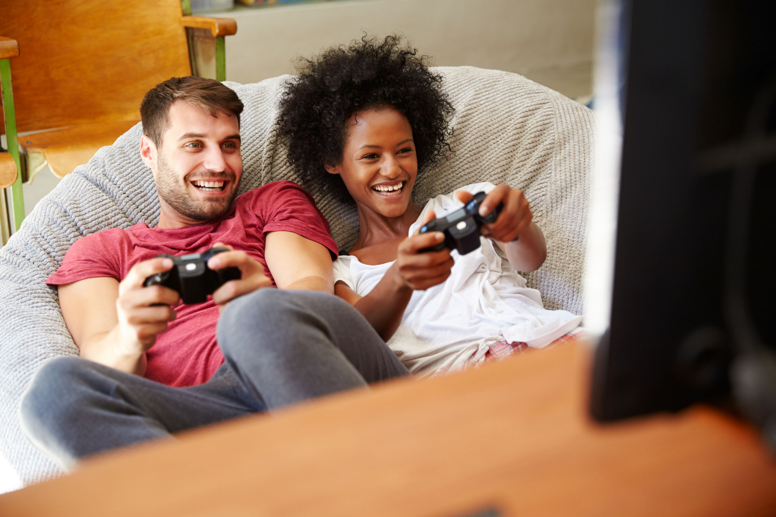 Young couple in pajamas playing together on Xbox One